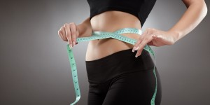 Closeup of a young and fit woman's waist with measuring tape